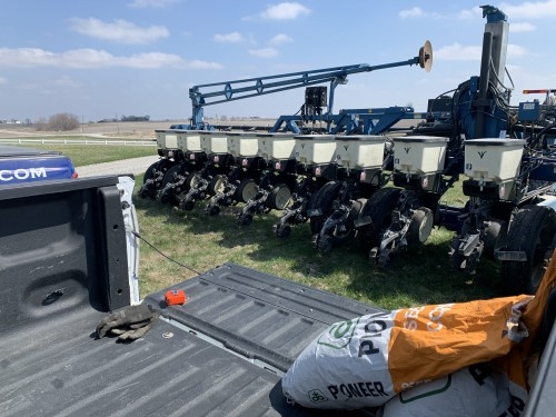 Kinze 16 row planter with a Pioneer seed bag in the bed of a truck